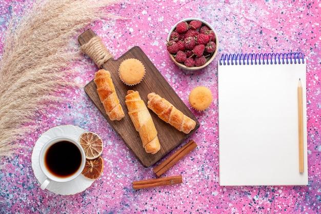 Vista superior de saborosas framboesas frescas dentro de um prato branco com pãezinhos de chá e canela na superfície rosa