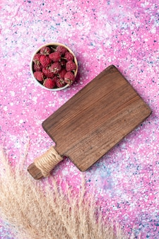 Vista superior de saborosas framboesas frescas dentro de um prato branco na superfície rosa