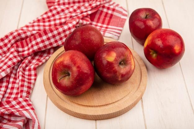 Vista superior de saborosas maçãs vermelhas em uma placa de cozinha de madeira em um pano xadrez vermelho sobre um fundo branco de madeira