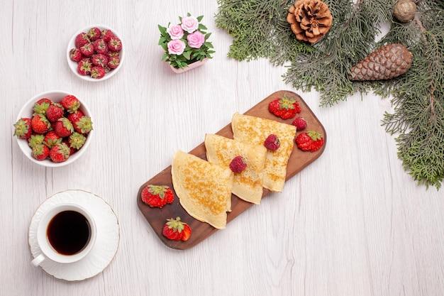 Vista superior de saborosas panquecas doces com frutas e uma xícara de chá em branco