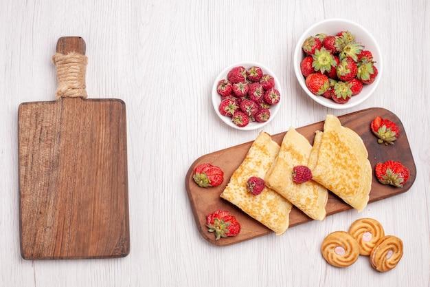 Vista superior de saborosas panquecas doces com frutas no branco