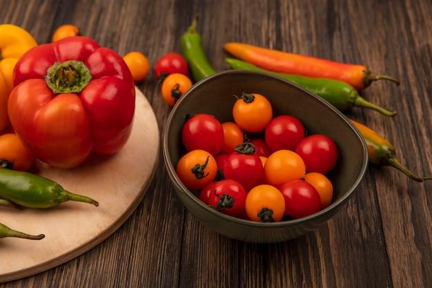 Vista superior de saborosas pimentas em uma placa de cozinha de madeira com tomate cereja em uma tigela na parede de madeira