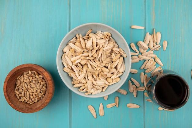 Vista superior de saborosas sementes de girassol brancas em uma tigela com sementes de girassol sem casca em uma tigela de madeira com um copo de coca-cola