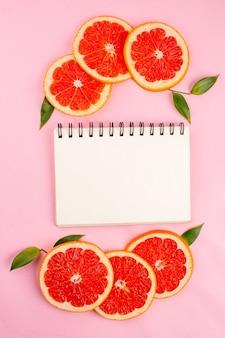 Vista superior de saborosas toranjas com bloco de notas na superfície rosa