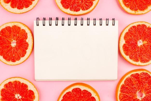 Vista superior de saborosas toranjas cortadas em fatias de frutas suculentas alinhadas na superfície rosa