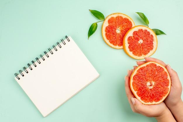 Vista superior de saborosas toranjas fatiadas suculentas com bloco de notas na superfície azul-clara