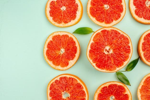 Vista superior de saborosas toranjas frescas alinhadas em uma superfície azul-clara