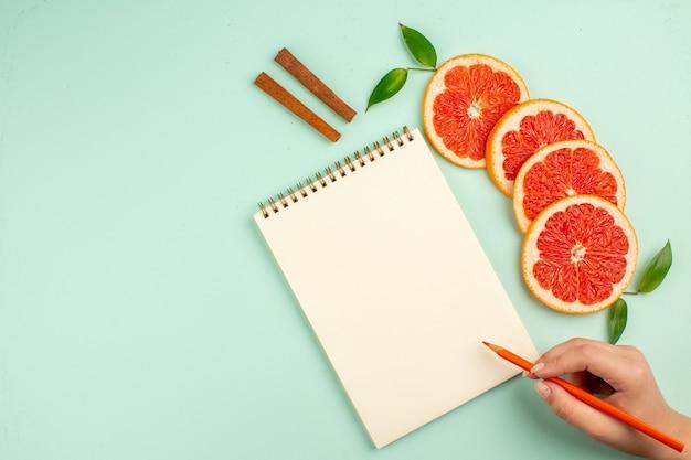 Vista superior de saborosas toranjas frescas com bloco de notas na superfície azul-clara