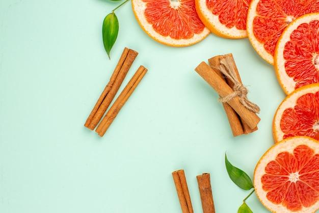 Vista superior de saborosas toranjas frescas com canela na superfície azul-clara