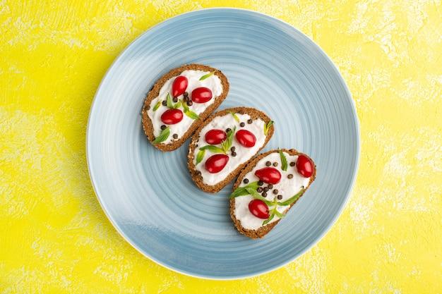 Vista superior de saborosas torradas de pão com creme de leite e dogwoods dentro de um prato azul no chão amarelo