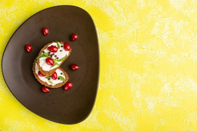 Vista superior de saborosas torradas de pão com creme de leite e dogwoods na superfície amarela
