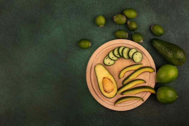 Vista superior de saborosos abacates com fatias em uma placa de cozinha de madeira com limão e feijoas isoladas em um fundo verde com espaço de cópia