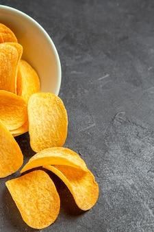 Vista superior de saborosos chips de queijo dentro do prato em fundo escuro