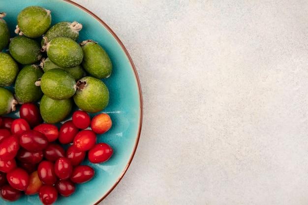 Vista superior de saborosos feijoas frescas com cerejas da cornalina em um prato azul em um fundo cinza com espaço de cópia