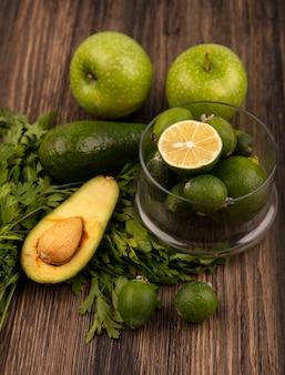 Vista superior de saborosos feijoas maduros com limão em uma tigela de vidro com maçãs verdes, abacate, feijoas e salsa isoladas em uma superfície de madeira