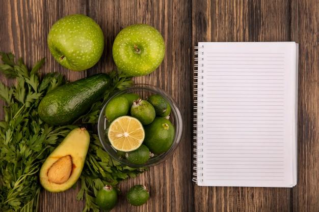 Vista superior de saborosos feijoas maduros com limão em uma tigela de vidro com maçãs verdes, abacate, feijoas e salsa, isolado em um fundo de madeira com espaço de cópia