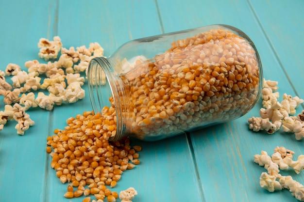 Vista superior de saborosos grãos de pipoca caindo de uma jarra de vidro com as pipocas isoladas em uma mesa de madeira azul
