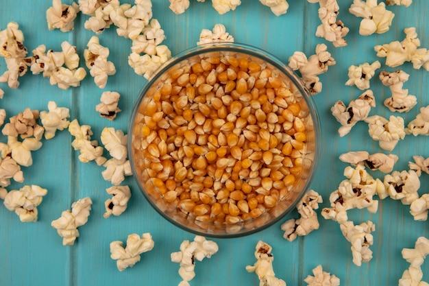 Vista superior de saborosos grãos de pipoca em uma jarra de vidro com pipocas isoladas em uma mesa de madeira azul