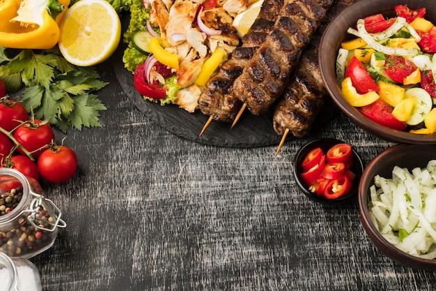 Vista superior de saborosos kebabs e outros pratos com ingredientes