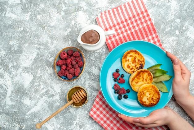 Vista superior de saborosos muffins com frutas vermelhas na superfície clara