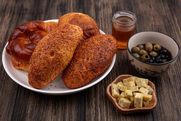 Vista superior de saborosos pães em um prato com azeitonas e fatias de queijo picadas em um fundo de madeira