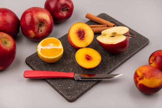 Vista superior de saborosos pêssegos em uma placa de cozinha preta com maçã tangerina e paus de canela com faca em um fundo cinza