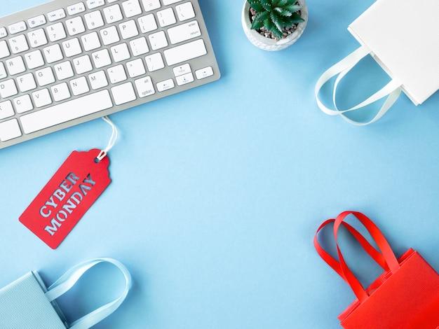 Vista superior de sacolas de compras com teclado e etiqueta para cyber segunda-feira