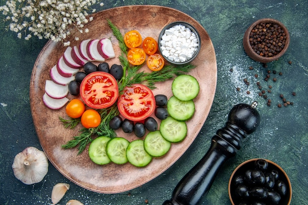 Vista superior de sal de azeitonas de vegetais frescos picados em um prato marrom e uma flor de alho de martelo de cozinha em fundo verde preto