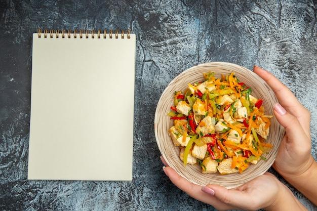 Vista superior de salada de frango com vegetais fatiados em superfície leve