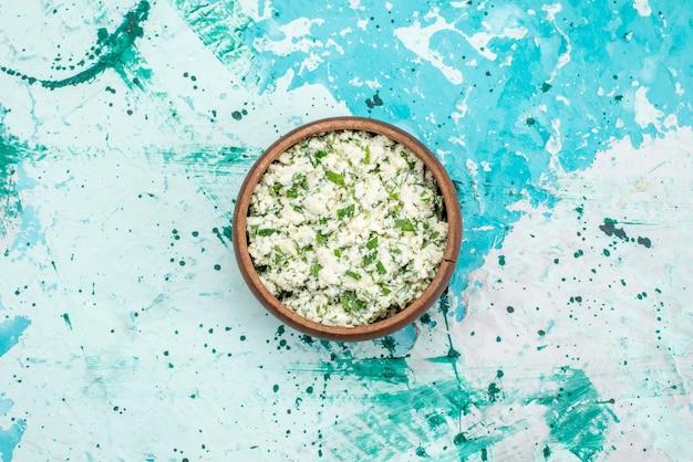 Vista superior de salada de repolho fatiado com verduras dentro de uma tigela marrom na mesa azul brilhante