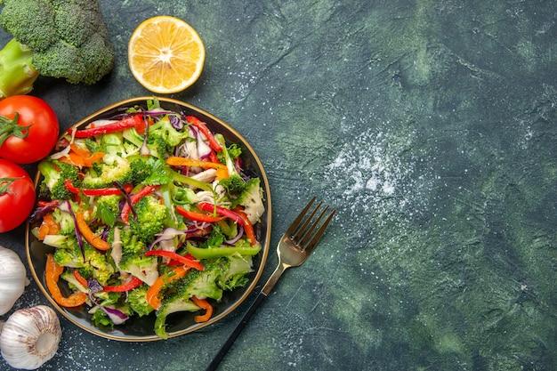 Vista superior de salada vegana em um prato e legumes frescos em fundo escuro