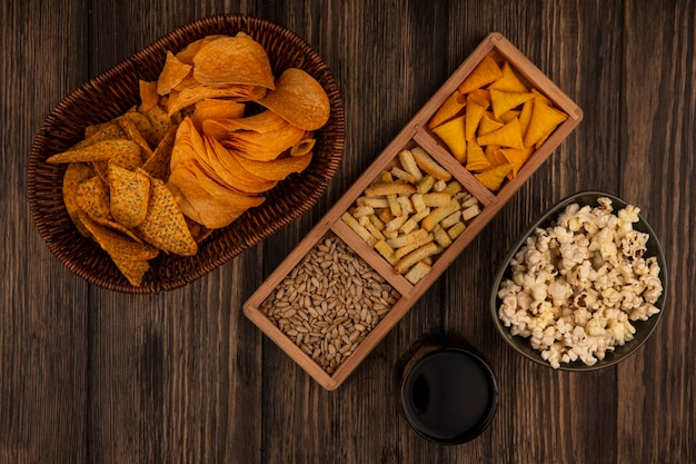 Vista superior de salgadinhos de milho em forma de cone em uma placa de madeira dividida com sementes de girassol sem casca com batatas fritas picantes em um balde com um copo de coca-cola em uma mesa de madeira