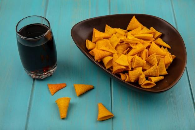 Vista superior de salgadinhos de milho frito em forma de cone em uma tigela com um copo de coca-cola em uma mesa de madeira azul