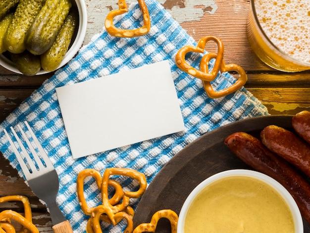 Vista superior de salsichas com pretzels e cerveja