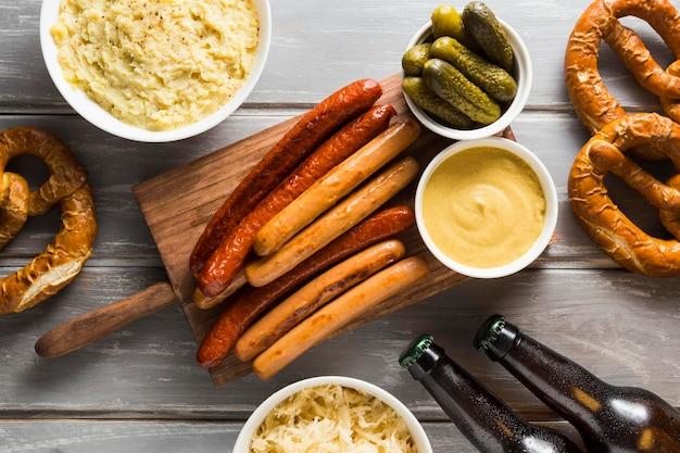 Vista superior de salsichas com pretzels e garrafas de cerveja