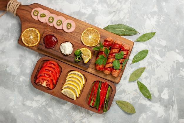 Vista superior de salsichas de diferentes composições de alimentos com tomates frescos e limões em uma foto colorida de mesa de refeição leve