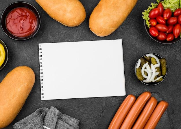 Vista superior de salsichas, pães e tomates