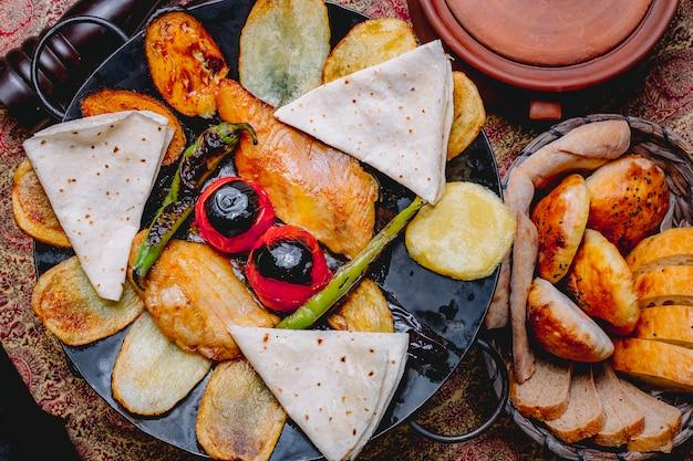 Vista superior de sálvia de frango com batatas legumes e pão pita