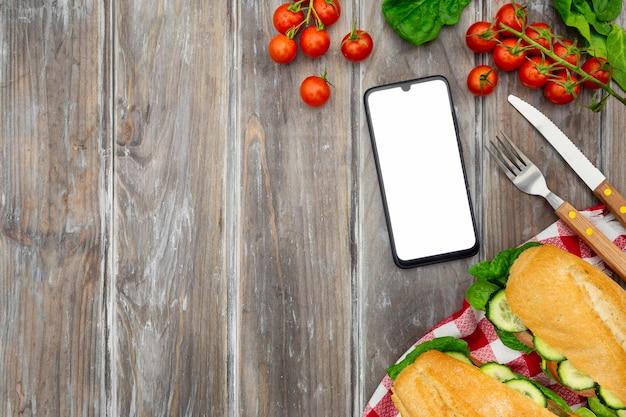 Vista superior de sanduíches com tomates e smartphone