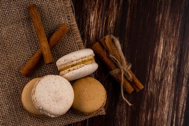 Vista superior de sanduíches de biscoito com canela de saco e no fundo de madeira com espaço de cópia