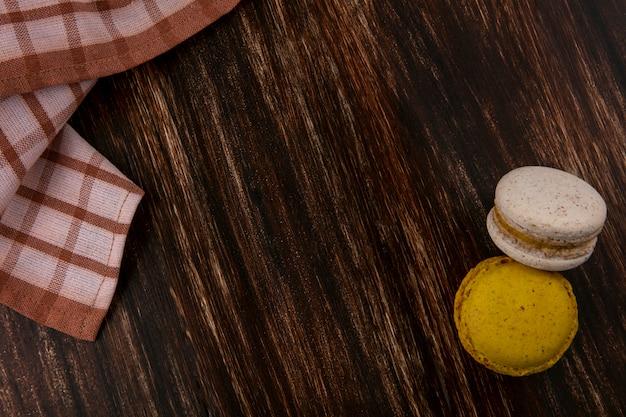 Vista superior de sanduíches de biscoito com pano xadrez em fundo de madeira com espaço de cópia