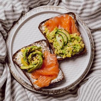 Vista superior de sanduíches de café da manhã na cama com salmão e abacate