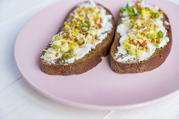 Vista superior de sanduíches de pão de centeio com queijo creme e brotou feijão mungo, nozes, girassol e linho. dieta de alimentos crus.