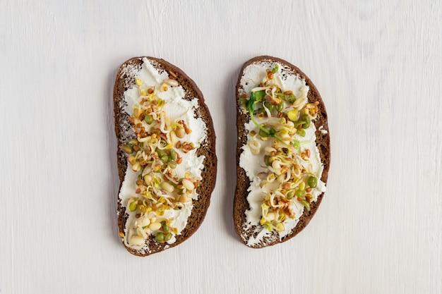 Vista superior de sanduíches de pão de centeio com queijo creme e brotou feijão mungo, nozes, girassol e linho em fundo de madeira.