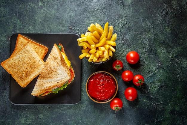 Vista superior de sanduíches de presunto com tomates vermelhos frescos e pasta de tomate na superfície escura