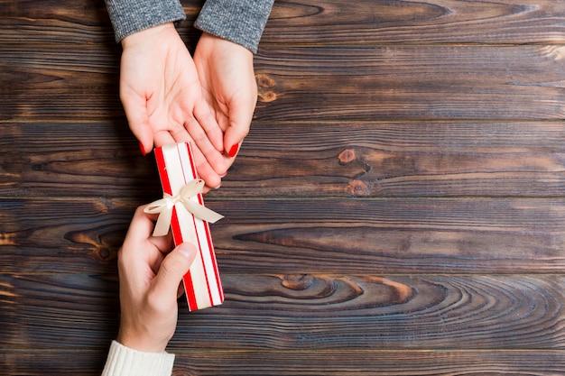 Vista superior de segurar um presente nas mãos femininas e masculinas na mesa de madeira. mulher e homem dão e recebem um presente. tempo para o conceito de férias com espaço de cópia