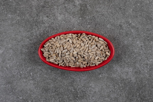 Vista superior de sementes de girassol frescas saudáveis em uma tigela vermelha.