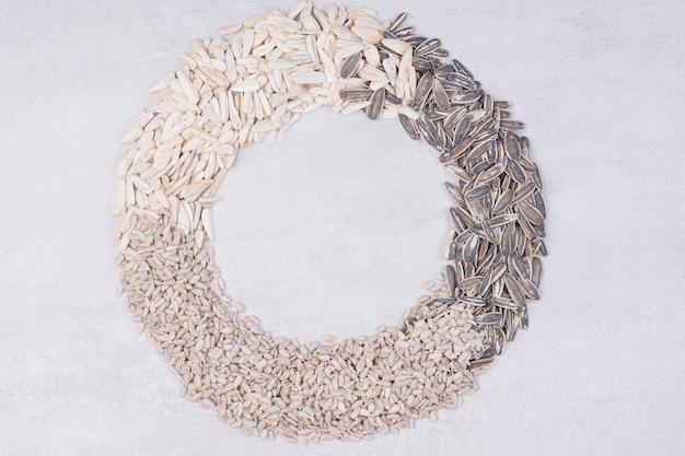 Vista superior de sementes de girassol mistas na superfície branca.