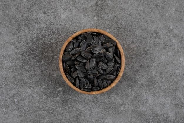 Vista superior de sementes de girassol pretas em uma tigela