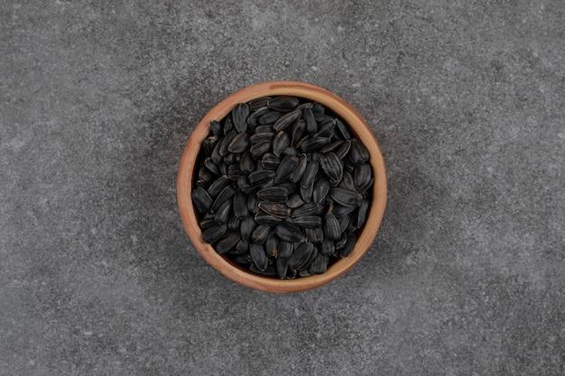 Vista superior de sementes de girassol pretas na superfície cinza